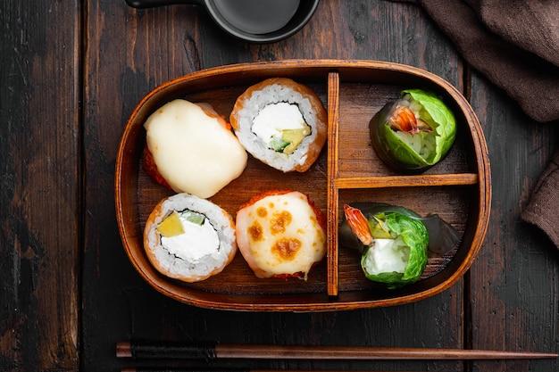 古い暗い木製のテーブルの背景に、箸がセットされた日本のお弁当箱、上面図フラットレイ