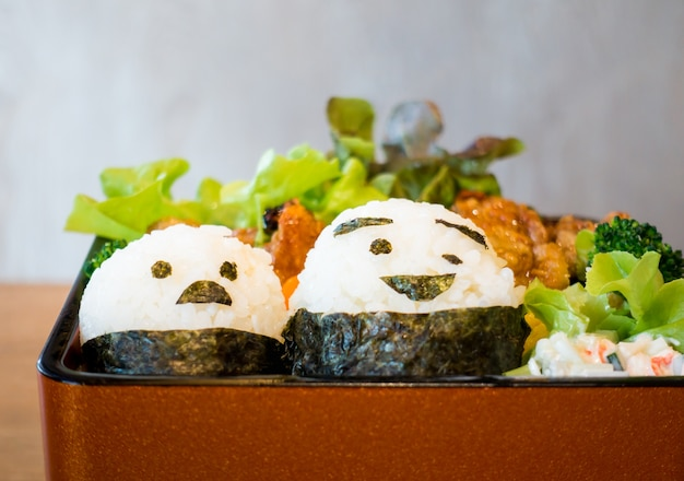 Japanese bento with smiley face on rice rolls.