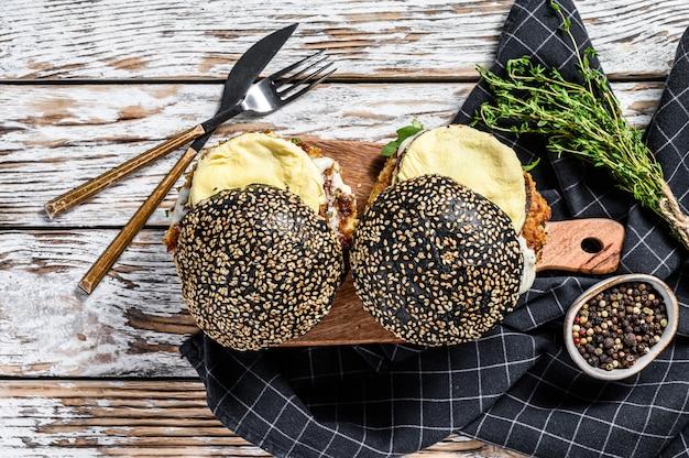 スクランブルエッグとルッコラの和風ブラックバーガー。黒いパンとチーズバーガー。上面図