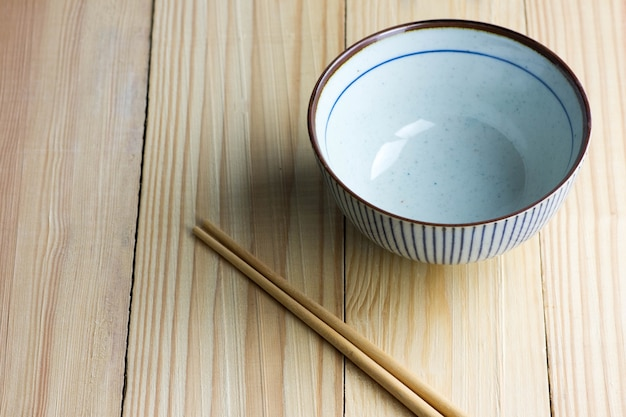 Japanese bowl and chopsticks on the wooden table.