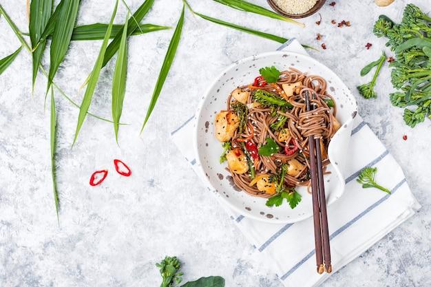 Японская гречневая лапша якисоба с курицей и овощами на светлом фоне