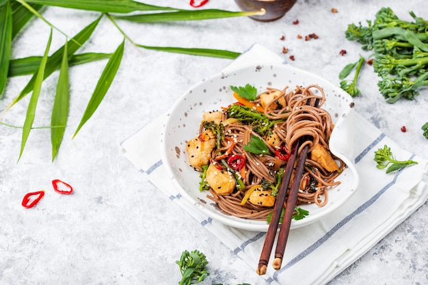 Japanese buckwheat noodles yakisoba with chicken and vegetables on a light background