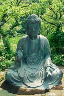Японская статуя будды в саду дзэн в камакуре, япония; сосредоточиться на статуе