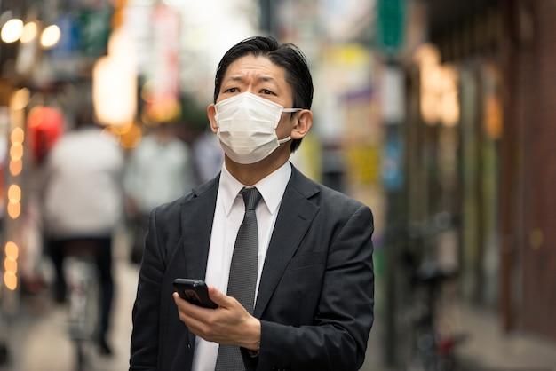 Японский бизнесмен в токио с деловым костюмом