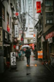 東京で透明な傘の下を歩く日本のビジネスマン