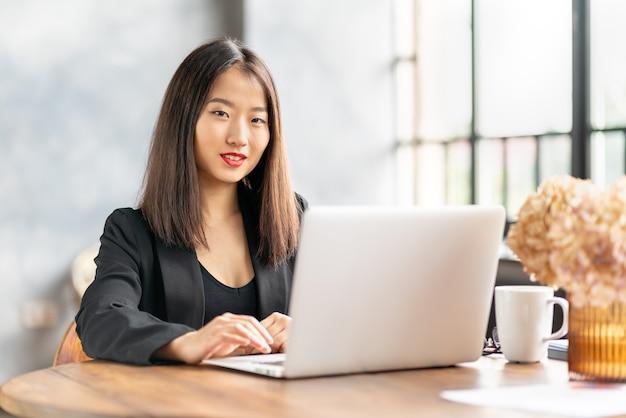 Японская деловая женщина работает в ноутбуке в кафе