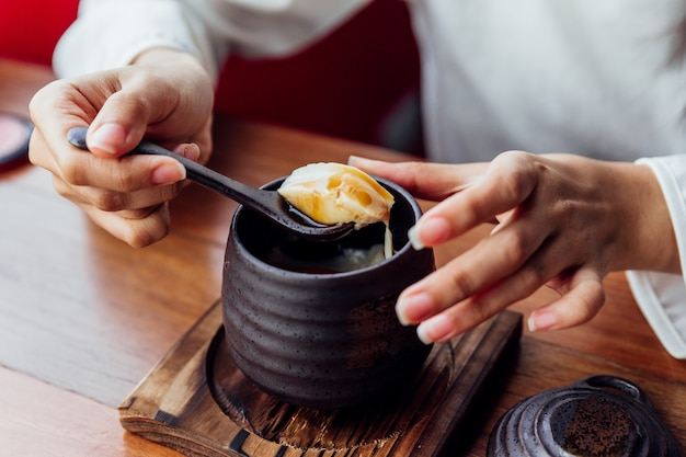 Japanese caramel pudding served in black ceramic cup that scoop soft pudding by woman hand