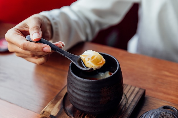 Japanese caramel pudding served in black ceramic cup that scoop soft pudding
