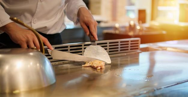 철판 구이 레스토랑에서 고기를 요리하는 일본 요리사