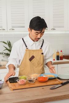 일본 요리사가 흰색 주방 초밥 재료에서 스시 롤을 요리하고 있습니다.