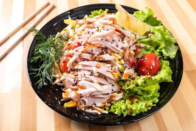 Японский куриный салат на черной тарелке. для любых целей.