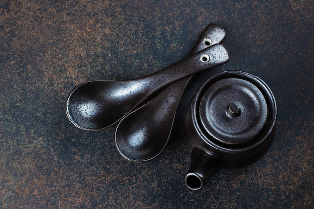 Japanese and chinese food equipment on dark stone concrete table background. spoons and kettle. top view with copy space