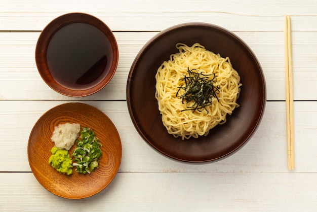Japanese cold ramen noodles with chopped green onions, grated wasabi and cup for dipping sauce