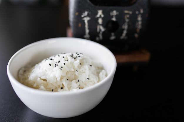 Japanese cooked rice in a white bowl on black table.