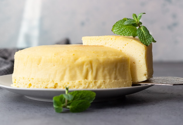 Japanese cotton cheesecake with mint on a grey plate.