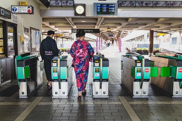伝統的な着物を持つ日本人カップルが自動改札機を通って進む