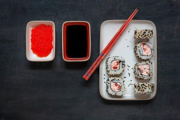 箸を使った大理石の石の板に赤キャビアを添えた日本のカニ肉のムース寿司