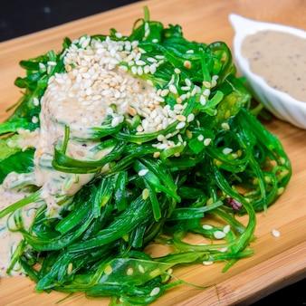 Японская кухня - салат из морских водорослей чука. подается с ореховым соусом и кунжутом.