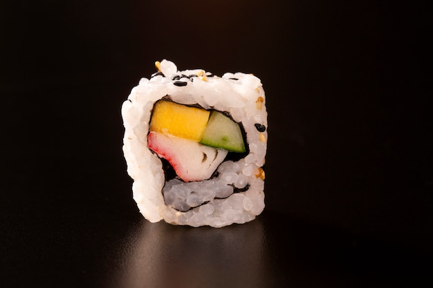 Japanese cuisine. one peace of sushi roll isolated on black background closeup shot