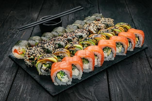 黒いテーブルに鮭マグロを添えた日本料理