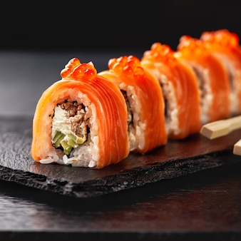 Japanese cuisine. salmon sushi roll in chopsticks on a stone plate over concrete surface.