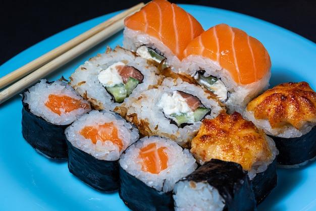 Japanese cuisine sushi rolls set on a blue plate