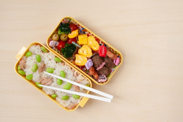 Japanese cuisine - traditional homemade bento box with rice, meat, egg, fish, vegetables and grains