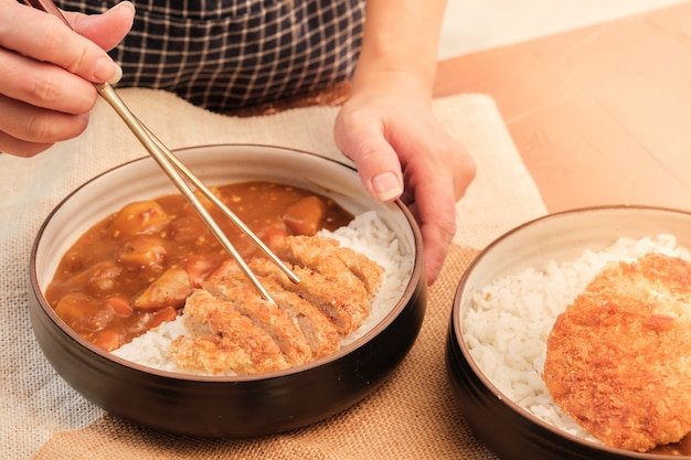 Japanese curry rice topping with fried pork and vegetables in white and black plate with chopsticks