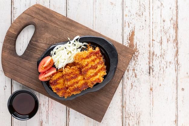Японская жареная свиная котлета или тонкацу с соусом, капустой и помидорами в черной керамической тарелке на старой деревянной разделочной доске на белом фоне деревянной текстуры с копией пространства для текста, вид сверху