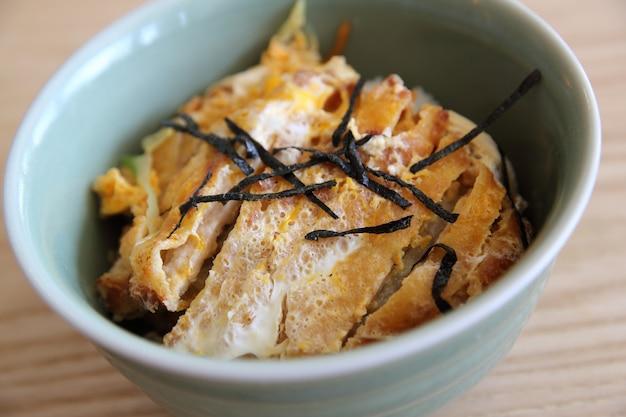 쌀에 계란을 얹은 일본식 튀긴 돼지고기, 나무 배경에 카츠동