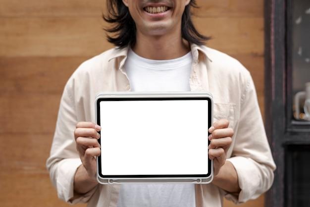 Japanese designer showing a digital tablet screen outside his sh