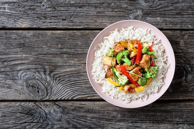 야채와 함께 일본 요리 카츠 치킨 카레 : 젓가락으로 제공되는 돌 표면에 분홍색 접시에 재스민 쌀 위에 브로콜리, 빨간색과 노란색 달콤한 고추와 파슬리 제공, 클로즈업