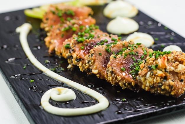 Japanese dish of tuna tataki served on a black stone plate