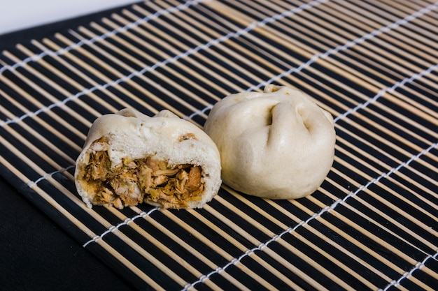Japanese dumplings with pork meat on placemat against black backdrop