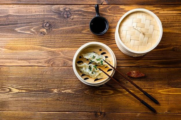 木材の背景に日本の餃子木製汽船。テキストのための伝統的なアジアのレシピスペース