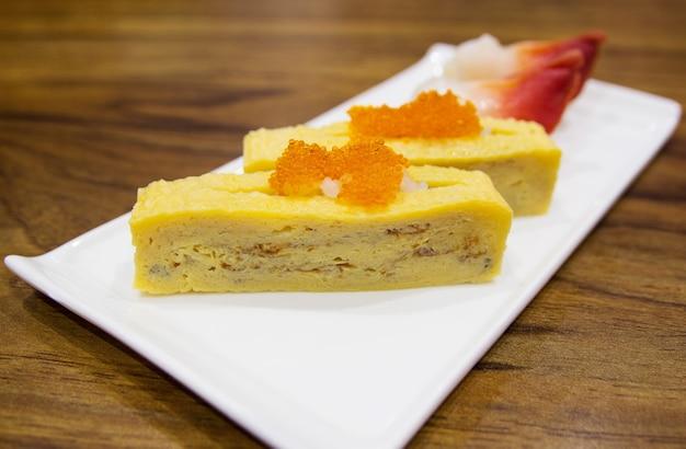白い皿の上にある日本の卵の寿司