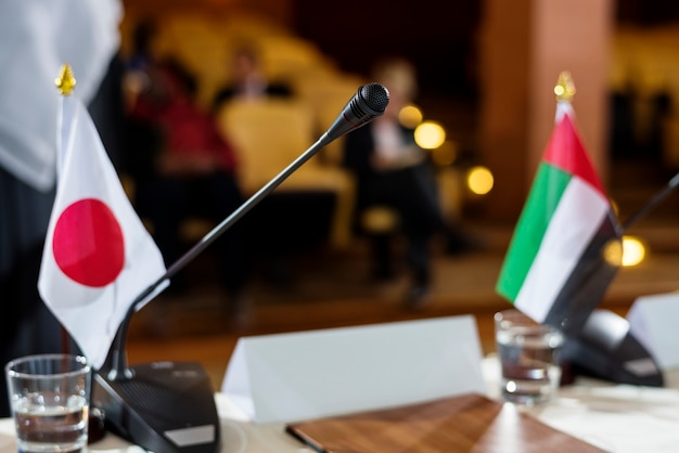 Japanese and emirati flags on a table with microphone in an international conference