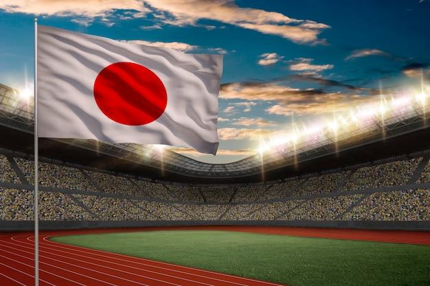 Японский флаг перед легкоатлетическим стадионом с болельщиками.