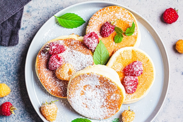 Japanese fluffy pancakes with raspberries in gray plate, gray background, top view. japanese cuisine concept.