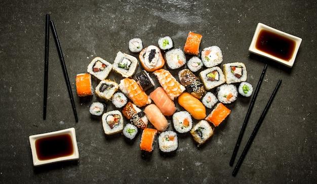 Японская еда. разнообразные роллы и суши с морепродуктами и соевым соусом.