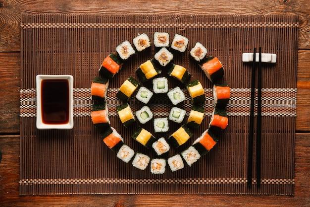 Японское кулинарное искусство. набор восхитительных роллов урамаки, красочный круглый орнамент суши, поданный на коричневой соломенной циновке, плоская планировка. фото меню роскошного ресторана.