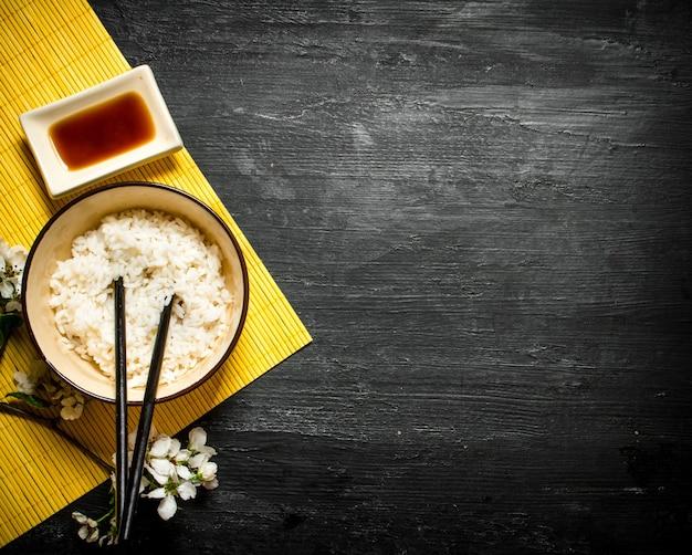 Японская еда. отварной рис с соевым соусом и ветками вишни