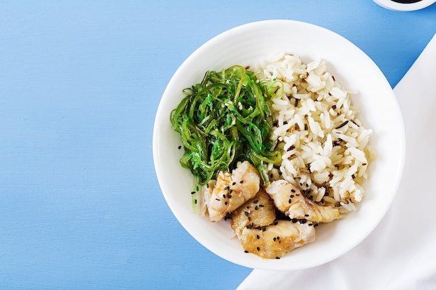 日本の食べ物。ご飯、白身魚のわかめ、わかめ中華または海苔サラダ。上面図。フラットレイ