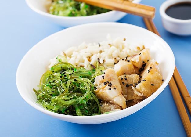 Японская еда. чаша из риса, отварной белой рыбы и вакаме чука или салат из морских водорослей.