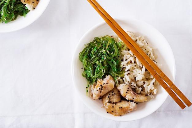 Japanese food. bowl of rice, boiled white fish and wakame chuka or seaweed salad.  top view. flat lay