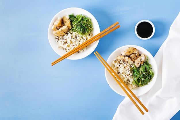 Japanese food. bowl of rice, boiled white fish and wakame chuka or seaweed salad.