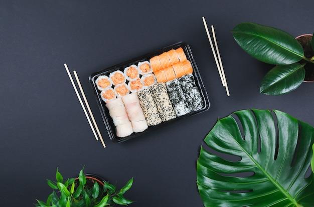 일본 음식 케이터링. 블랙 테이블에서 젓가락으로 스시