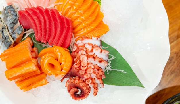 日本食コンボセット。鮭、マグロの刺身、ミズダコ、カニの棒は、レストランのテーブルの白い皿に砕いた氷を添えて出されます。