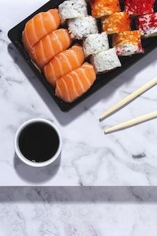 Концепция японской кухни. ассорти суши на вынос в коробке. с собой. доставка. морская еда