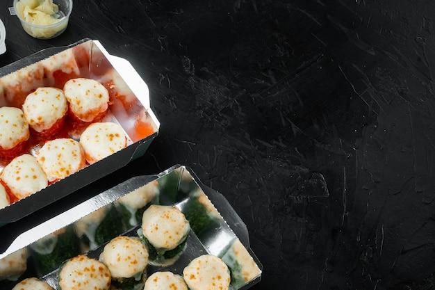日本食のコンセプト。ケータリング、さまざまな種類の寿司フィラデルフィアロールと焼きエビロールが黒い石の上にセットされています